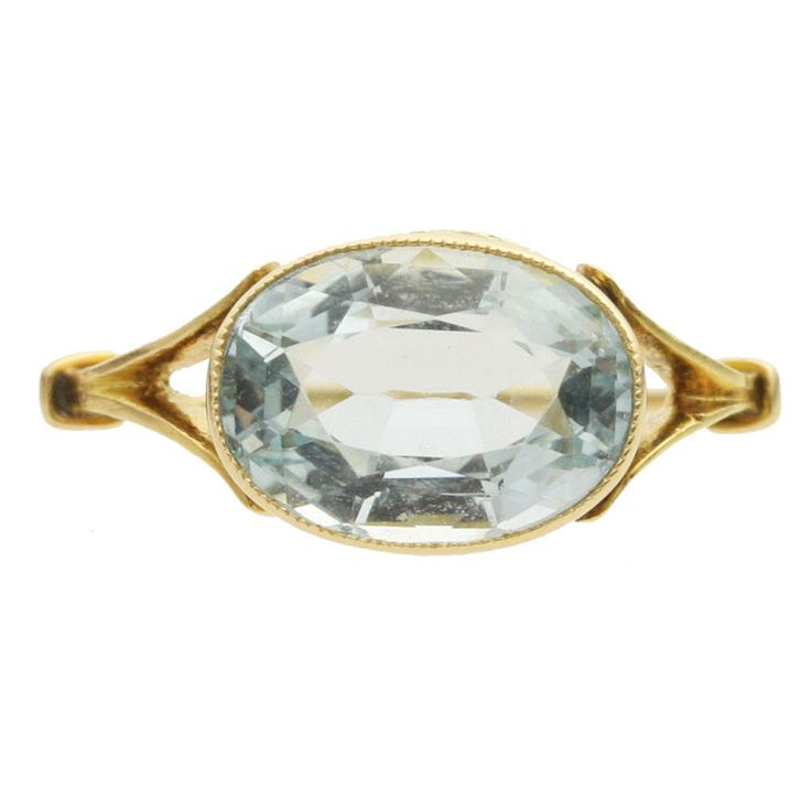 Aquamarine Ring, c. early-to-mid 20th century, 18k yellow gold, one 2.23 carat oval brilliant aquamarine of light-toned,, very slightly greenish blue  Aquamarine is rarely set in yellow gold, making this pretty split-shoulder 18k gold ring a rare treasure. A lovely, clean 2.23 carat oval brilliant-cut aquamarine is elegantly millegrain bezel-set at an unusual horizontal angle, making the most of its hand-filling size.