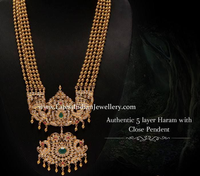 Authentic 5 layer gold balls long haram attached with close setting diamond step pendant. The diamond rani haar with double step diamond peacock pendant looks royal.