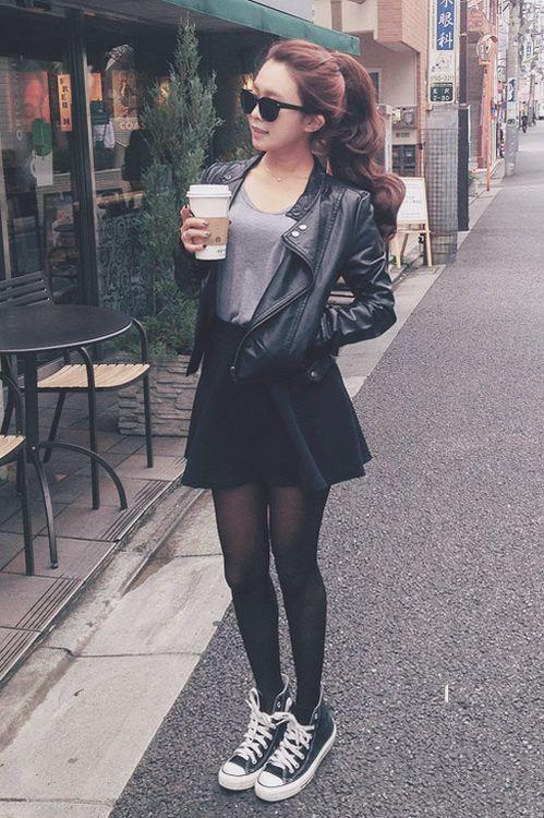 gray shirt. black skirt. leather jacket. black pantyhose. black converse