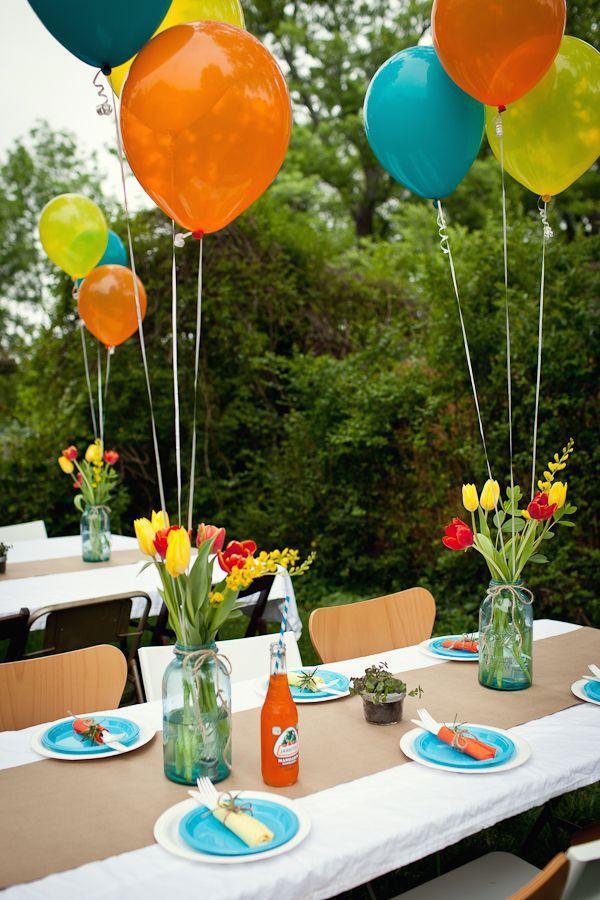 Centros de mesa de frascos de vidrio celeste. Cada centro de mesa tiene tulipanes rojos y amarillos y tres globos con helio de colores anaranjado, celeste y amarillo.
