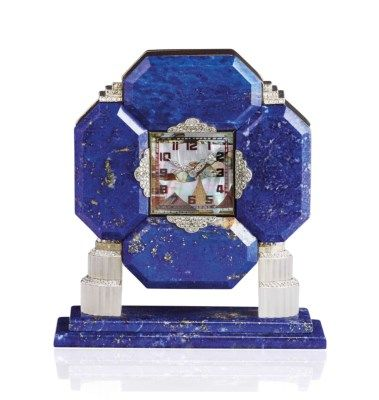 AN ART DÉCO LAPIS LAZULI, MOTHER-OF-PEARL, LACQUER AND ROCK CRYSTAL CLOCK The square dial depicting a rural scene in mother-of-pearl marquetry, with red and black Roman numerals and diamond-set hands, to the four octagonal lapis lazuli surround with diamond-set panel accents, the back in black lacquer, set on a lapis lazuli and rock crystal base, 1930s;  sold 50,000 CHF;  14/11/17.