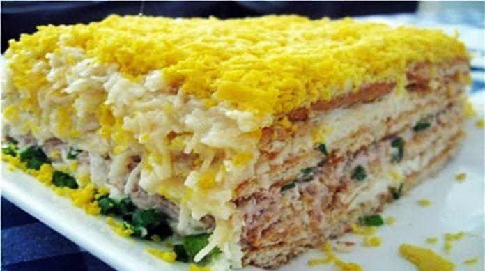 яйца — 5 штук;сыр — 150 грам рыбная консерва — 1 банка; крекер несладкий — 500 грамм; огурцы маринованные — 4 шт. чеснок — 2 зубка; майонез — 200-250 грамм. Отделите белки от желтков. Белки смешайте с майонезом. Сыр натрите на терке, добавьте  чеснок, и майонез. Огурцы порежьте мелкими кубиками. Выкладываем 1/3 часть крекера, затем белок с майонезом, крекер, помятую вилкой консерву, огурцы, затем снова крекер, слой сыра с майонезом. Украшаем натертым на мелкую терку желтком.