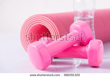 Yoga mat with dumbbells and bottle of water.
