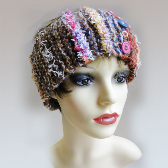 Luxury hand crafted head band, hand knitted with a variety of pink rustic reds, browns and orange colours. This luxury chunky broad head headband is finished off with a variety of  hand made paradis terrestre luxury braids and hints of furry creams with a multi-coloured button detail