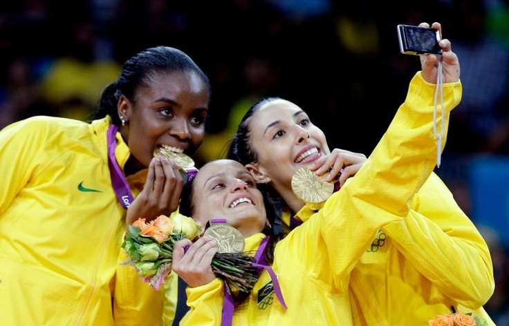 Brazil's, from left, Fabiana Claudino, Fabiana Oliveira, and Sheilla Castro pose for a photo after winning the gold medal for women's volleyball at the 2012 Summer Olympics Saturday, Aug. 11, 2012, in London. (AP Photo/Chris O'Meara)