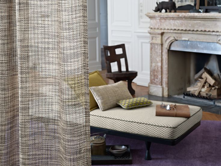 Living room, chimney, fireplace, curtain, drpaery, cushions.  This latticework fabric with a handmade look consists of multicoloured moiré yarns and impresses with a surprising transparent effect when it is held against the light. This lends an elegant heaviness to the room's atmosphere while keeping the area at the window relatively bright.