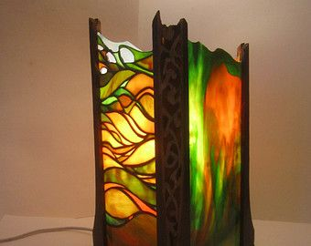 one-of-a-kind hand-made stained glass and slate stone lantern. Slate was carefully chipped and shaped to fit together and assembled with the stained glass pieces. The dimensions of each side are approximately 5.5 x 11.5 inches and were assembled using the copper-foil method. The lantern sits on a stained solid maple wood base and comes wired with a 8 ft. cord. This is a relatively large, tall lamp.
