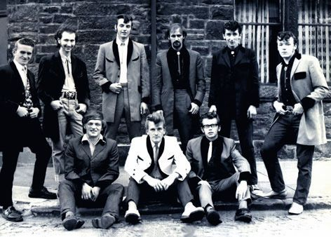 1950's teddy boys: a British subculture typified by young men wearing clothes that were partly inspired by the styles worn by dandies in the Edwardian period, styles which Savile Row tailors had attempted to re-introduce in Britain after World War II. Strongly associated with American rock n roll