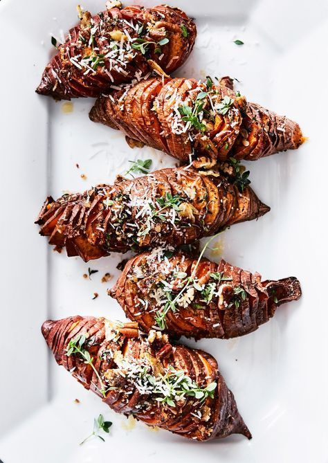 Hasselback Sweet Potatoes with Thyme, Pecans and Parmesan | Our twist on a Thanksgiving favorite! We top sweet potatoes with a savory, nutty topping of fresh thyme, Parmesan cheese and pecans.