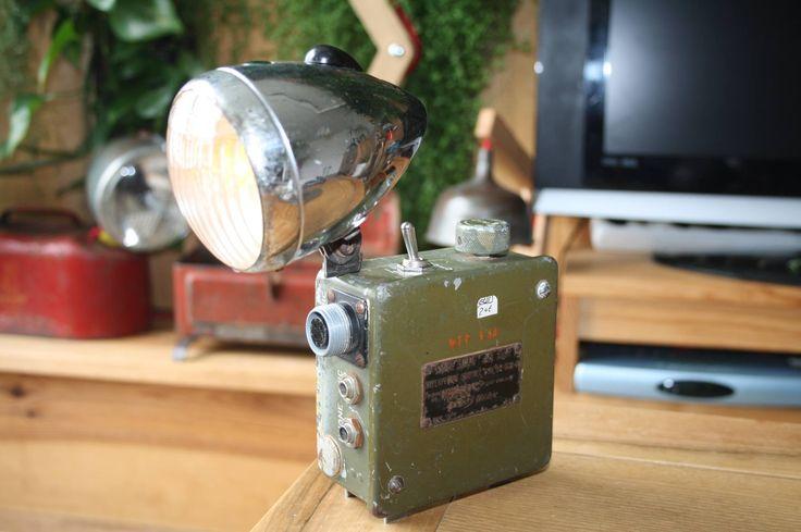 Lampe de chevet type baladeuse fonctionnant sur batterie. Réalisée avec un boitier radio BC606D Western électrique de l'armée américaine lors de la seconde guerre mondiale, véritable pièce historique en voie d'épuisement.  Surmontée d'un vieux phare de vélo offrant trois positions d'éclairage, veilleuse ,code et plein phare.