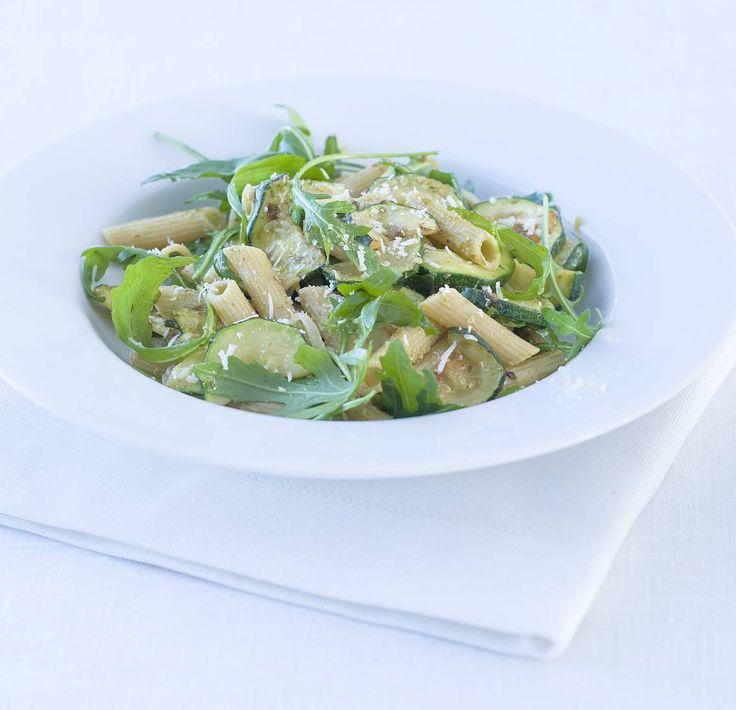 Penne pesto met courgette  Zo maak je het! Kook de pasta in ruim water met zout volgens de aanwijzingen beetgaar.  Verhit in een koekenpan de olijfolie. Fruit de ui. Voeg de courgette toe en bak in 5 min. bruin en beetgaar.  Giet de pasta af en vang een kopje kookvocht op. Meng de pasta met de pesto en een scheutje kookvocht door de courgette.  Schep er de rucola door en breng op smaak met zout en peper. Verdeel de penne over 4 diepe borden en bestrooi met de kaas.