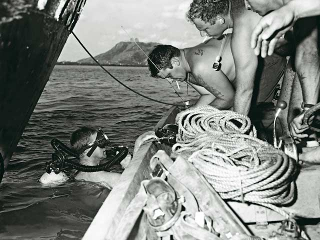 """RAN divers Able Seaman Clearance Diver Mike Ey in the water at Cat Lo, Vung Tau, and Chief Petty Officer Clearance Diver Vic Rashleigh with an unidentified American diver. The group was clearing two 4.2 mortars from the propellers of a Philippine tug. [Image courtesy of Norm Cooper]"""