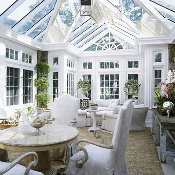 Conservatory dining room & living room with white walls & furniture