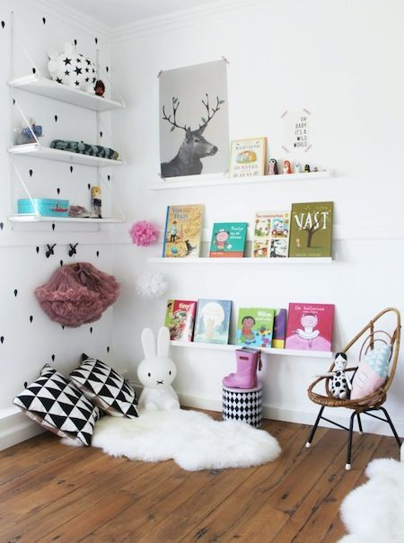 A cozy sheepskin rug and a wall of books create the perfect corner for your little one to read books and daydream