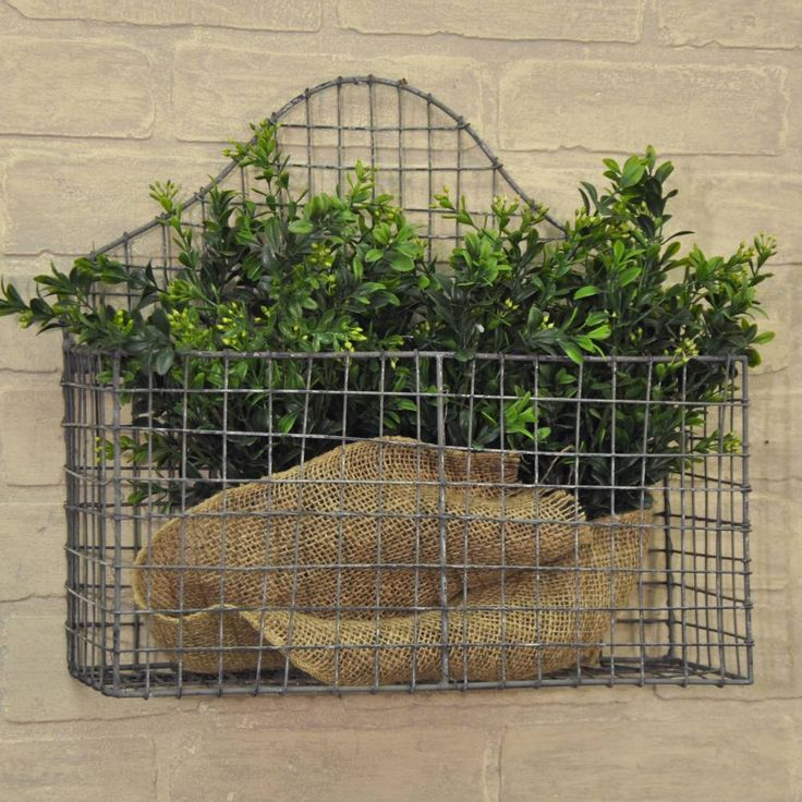 """Ideal for any part of your home, this wall basketfits right in with any farmhouse or country cottage decor. Organize magazines to eliminate clutter or add color and beauty to your decor with faux greens or flowers. Cottage Wire Wall Basket Galvanized wire 14""""H x 15""""W x 5""""D"""