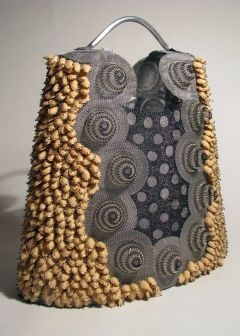 "Lindsay Ketterer Gates' ""Neckline Basket""  Lindsay Ketterer Gates, a Pennsylvania resident, uses rare techniques, fashion design and mundane materials to create three-dimensional works that muster curiosity and surprise. Her pieces stand beside interesting vessels made of citrus peels and waxed linen by California artist Jan Hopkins."