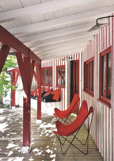 En rouge et blanc, la terrasse couverte s'inspire du Pays Basque - Joyeuse maison au Cap Ferret - CôtéMaison.fr