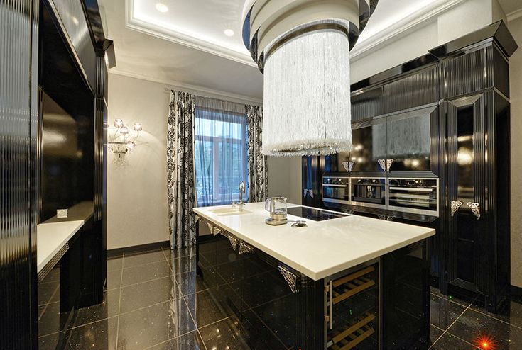 Eclectic kitchen with black cabinets white counters and amazing hanging light fixture