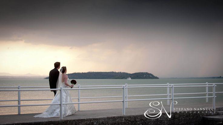 Wedding couple walking with a storm behind on the trasimeno lake #umbria #trasimeno lake #weddinginitaly  #weddingphotographer