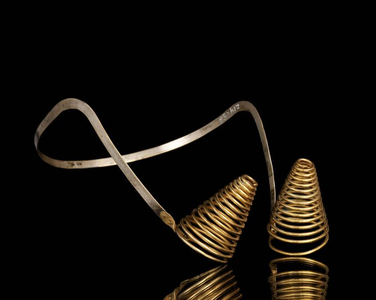 1900-1910 Messing oorijzer met grote taps toelopende krullen, bestaande uit 14 windingen. Deze zijn met klinknageltjes aan de messing beugel vastgezet. Gedragen in Heenvliet, door een vrouw in de streekdracht van de Zuid-Hollandse eilanden. #VoornePutten #ZuidHolland