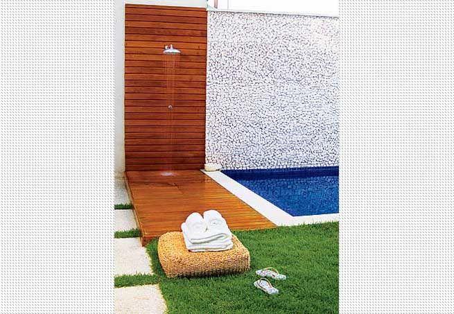 O revestimento de madeira cumaru mantém a área do chuveiro delimitada, além de destacar a parede de mosaico português que acompanha a piscina