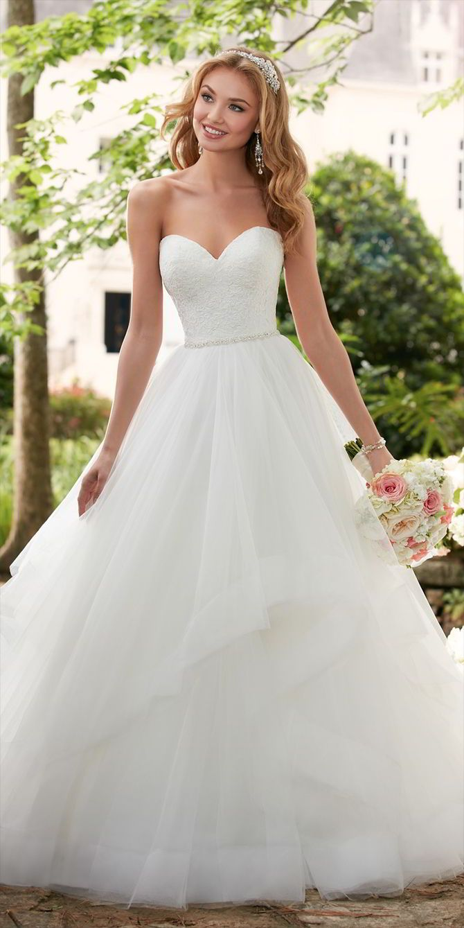 This layered ball gown wedding dress from Stella York is a princess bride's dream come true! Layers of frothy tulle create volume through asymmetrical horsehair hemlines. A lace covered bodice with a strapless sweetheart neckline is reminiscent of traditional ball gowns but this wedding gown is given an update with a Diamante belt that shimmers at the waist. An easy-close zipper is hidden under fabric buttons for the perfect fit.