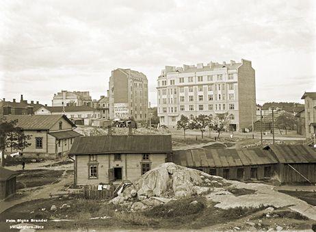 Pengerkadun (nykyään Kinaporinkatu), Vaasanpolun ja Helsinginkadun muodostama kolmiomainen aukion hahmottaa puutalojen takaa. Signe Brander 1912.