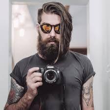 Corte de cabelo masculino comprido com sidecut e franja mais comprida em camadas jogada para o lado.