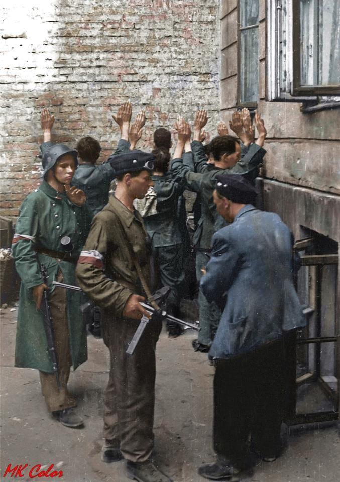 Śródmieście Północne. Jeńcy niemieccy z załogi PAST-y pilnowani przez powstańców na podwórzu kamienicy przy ulicy Zielnej 34. Na pierwszym planie powstaniec z niemieckim pistoletem maszynowym MP-40 Zródło:MPW