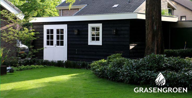 Ruim tuinhuis met zwart geschilderde douglashout planken. Bevestigd volgens de potdeksel methode.