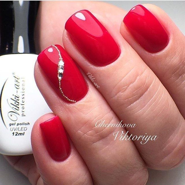 Красный маникюр с изящной инкрустацией стразами и микробисером на ногте безымянного пальца