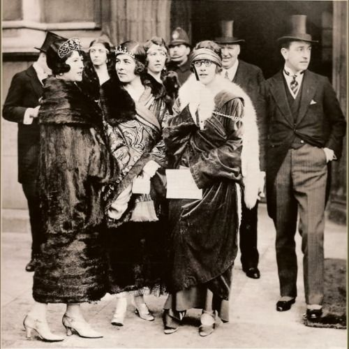 """The Milford-Havens, 1924. """"From left to right: Nada, Marchioness of Milford Haven, the Countess of Airlie, Lady Zia Wernher and George, 2nd Marquess of Milford Haven at the State Opening of Parliament, 15th January,1924. Nada and Lady Airlie are attempting to wear their ancestral tiaras in the fashionable manner, low on the brow, in the style that the fashionable bandeau tiaras were meant to be worn; they both have shingled hair as well."""""""