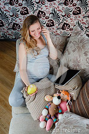 Pregnant woman resting on the sofa and talking on the phone. Pregnant concept