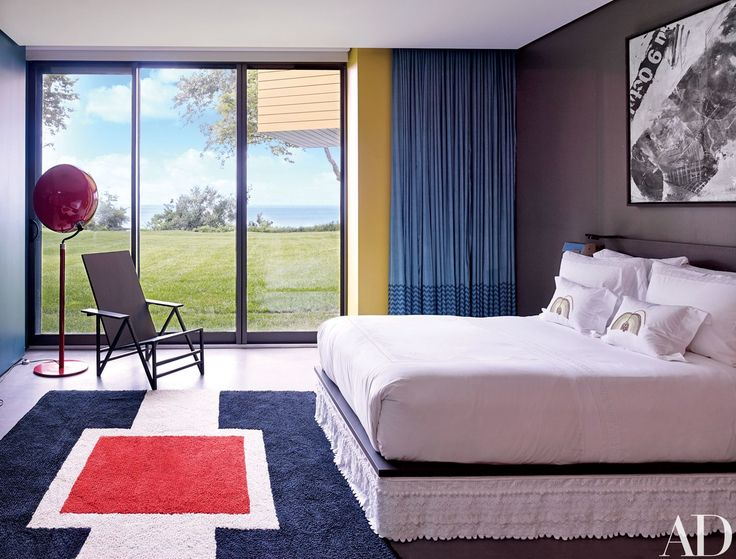 A '50s Italian floor lamp, a Gerrit Rietveld–style chair, and a vintage graphic rug animate a bedroom; the bed linens were hand-embroidered in Vietnam.