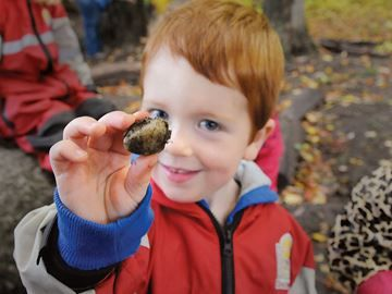 Barrie students exploring great outdoors at Forest School - Aidan Robertson checks out a rock he found while looking through the forest near Discovery Child Care Centre. The centre has started a forest school, which takes kids into nature three times a week, rain or shine.