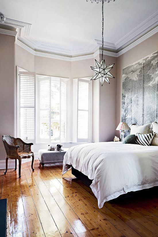 paint draws high ceiling down, lots of light reflected by the glossy wood floors, light fixture and art on one wall draw the eye, neutrals create relaxing atmosphere
