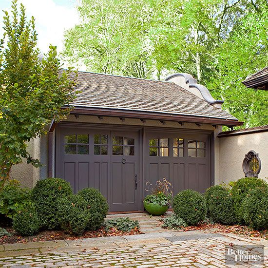 Although consideration of your house's details are important to the design of a detached garage, other hardscape pieces can lend inspiration, too. Here, the structure is integrated with a fence -- the wall extending seamlessly into the yard's borders -- and a curved roof detail replicating other fence features.