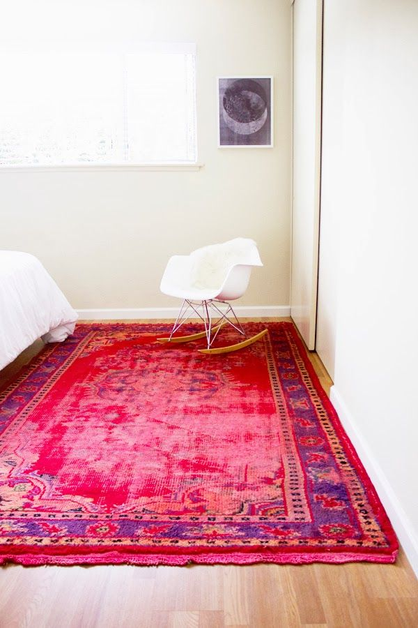 A vividly-colored overdyed rug can become the perfect focal point for a simple room defined by neutral colors. Consider adding one to the bedroom as a splash of color.{found on eatsleepcuddle}.