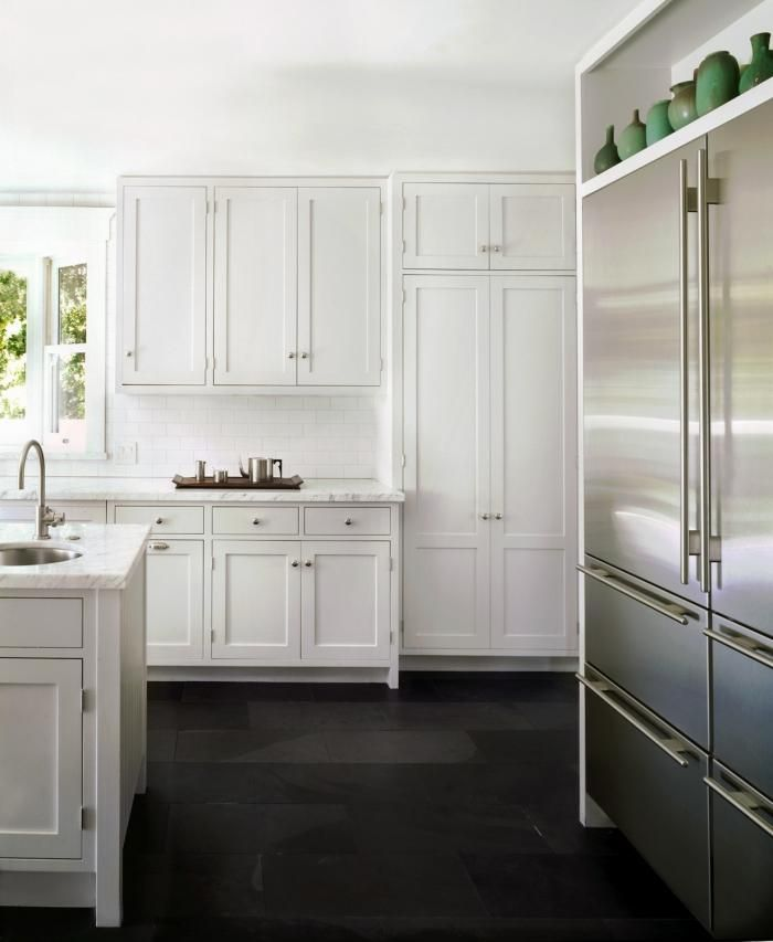 Carlson sought to keep the palette simple; she used a black slate floor, which provides contrast with the statuarietto marble counters and the cabinetry painted in Blackened by Farrow & Ball. A white Caravaggio P0 pendant lighting hangs over the kitchen island.    via @Remodelista
