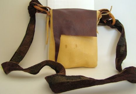 Deer skin body, flap and strap attached with deer skin ties, fabric strap tied to wooden rings be aware that there are various marks and irregularities in the leather. 6 1/2 inches wide 7 3/4 inches tall 49 inches total length of adjustable strap