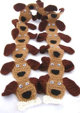 This free crochet pattern shows you how to make a puppy dog scarf. The dog holds a bone in its mouth at the end of the scarf.