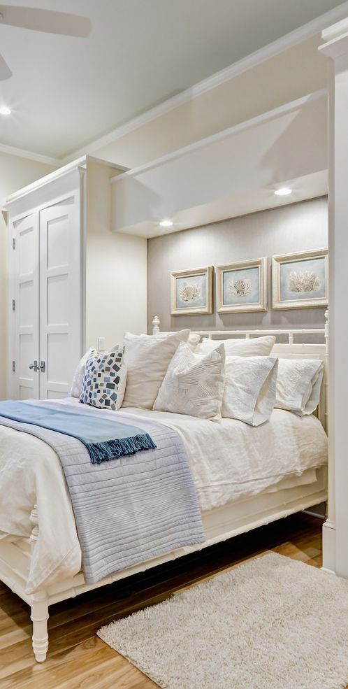 built in wardrobe, lots of pillows, pictures over the headboard, over the bed lighting