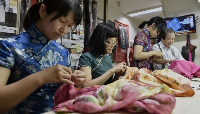 Taiwanese qipao maker Lin Chin-te (far right) works with his students at his studio in Taipei. Photo: AFP