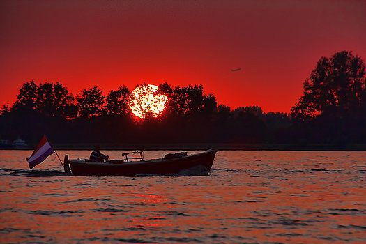 A beautiful sunset as the sun turns the sky red and turns the water into a wonderful mix of colors. Dutch countryside, a man and his boat on the water at sunset.