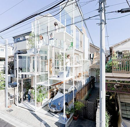 """Modern single family house with floor-to-ceiling glass windows is located in a quiet neighborhood in Tokyo, Japan.        Designed by Sou Fujimoto architects, unique house features strong metal frame, movable stairs, wooden furniture, and integrated parking space.        At night, """"glass walls"""" are covered with curtains. [photos by Iwan Baan]"""