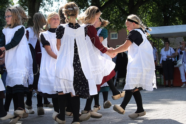 "These children, in the Dutch province ""Drenthe"", on wooden shoes and traditional costumes are part of a children dancing group from the town  Exloo in Drenthe."
