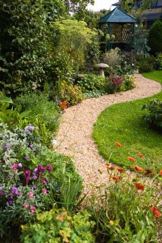 English cottage garden, winding shingle path leading to a gazebo between grass lawn and flowerbed of