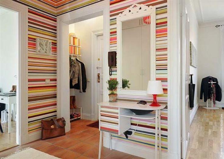 Un hall con mucho color y separado en 2 partes. En el espacio más pequeño junto a la puerta, un perchero. En el hall distribuidor, consola con espejo.