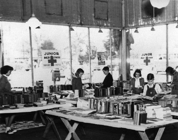 1943. Victory Book Campaign. Junior Red Cross members of the schools of LaGrange, Hogansville and Troup County, collecting a total of 1,326 books which were shipped to the Receiving and Distributing Center in Columbus, Georgia.  A vacant store building in the central business section was secured to display books contributed in the campaign, and Juniors, shown in the photograph, are sorting the books for packing and shipping.