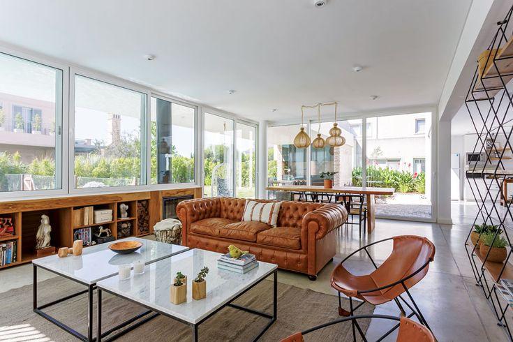 Living comedor integrado súper moderno y luminoso en una casa en Nordelta. Sillones de cuero y mesa ratona de mármol y acero, con biblioteca en varillas de acero.